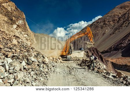 LADAKH, INDIA - SEPTEMBER 10, 2011: Excavator cleaning road after landslide in Himalayas. Ladakh, Jammu and Kashmir, India