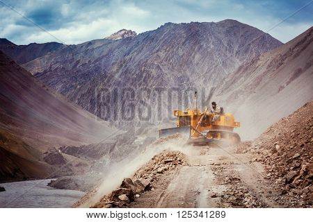 LADAKH, INDIA - SEPTEMBER 10, 2011: Bulldozer cleaning road after landslide in Himalayas. Ladakh, Jammu and Kashmir, India