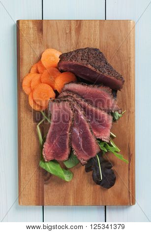 Rare beef steak with carrot and rocket salad on wooden board