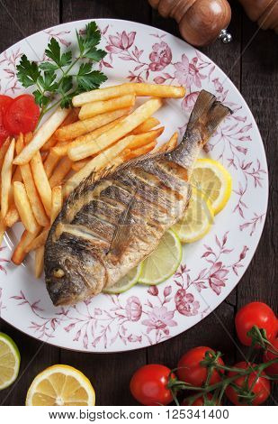 Grilled bream fish with french fries and lemon