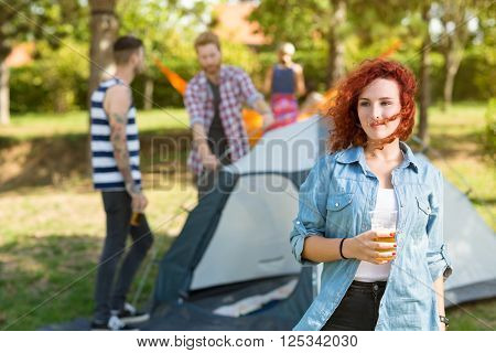 Ginger female with glass of beer stands in youth camp in greenwoods
