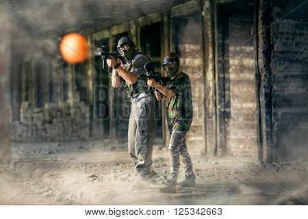 Two paintball player together in action