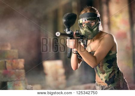 Paintball, female player with marker gun