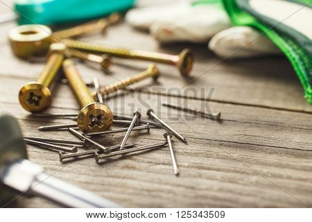 cross head bolt screws thread with nails on wooden desk closeup with copy space.