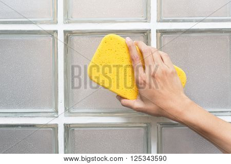 woman hand in yellow glove with sponge on glass blocks