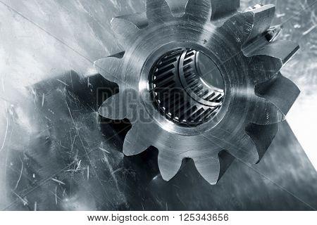 cogwheel in titanium with brushed aluminum background