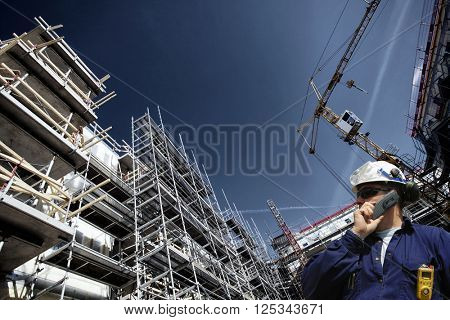 contruction worker, building site and cranes