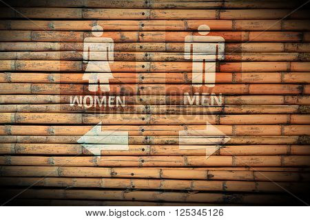 Toilet Signs male and female on brown bamboo wood wall