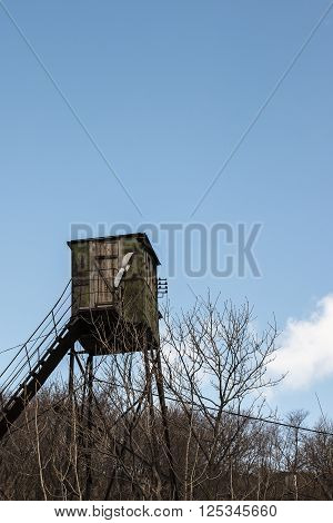 old observation tower on the background of trees without leaves