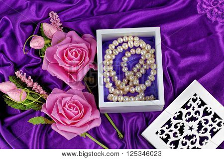 Pearl necklace in white box with flower with purple satin background