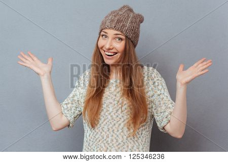 Cheerful woman shrugging shoulders over gray background