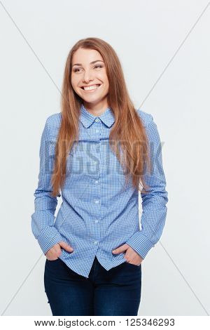 Smiling casual woman standing isolated on a white background and looking away