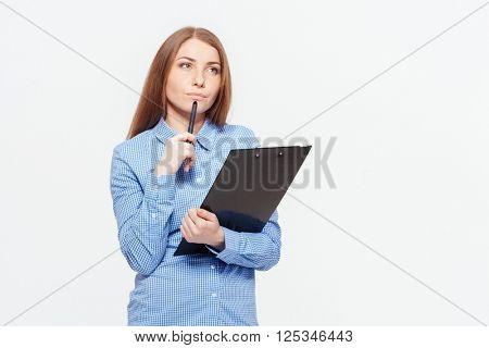 Thoughtful woman with clipboard standing isolated on a white background
