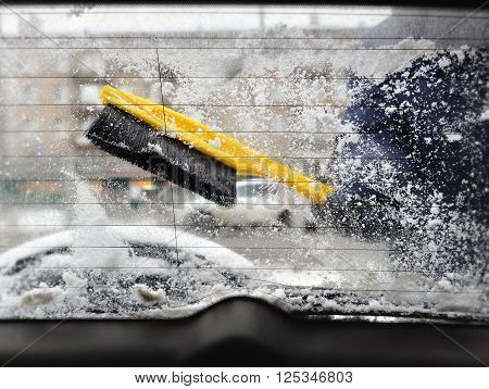Cleaning of a back car window of snow with use of a yellow brush. A look from within salon. Through muddy wet glass are visible winter street with building passing car part of a spare wheel and silhouette of the man cleaning glass.