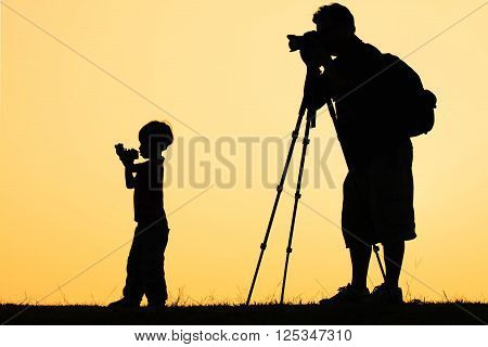 silhouette of photographer shooting photo for a sunrise