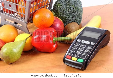 Payment terminal credit card reader and fresh fruits and vegetables with plastic shopping carts cashless paying for shopping finance concept