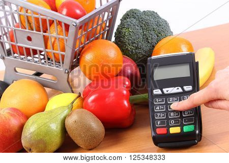 Hand of woman using payment terminal enter personal identification number credit card reader and fresh fruits and vegetables with plastic shopping carts cashless paying for shopping