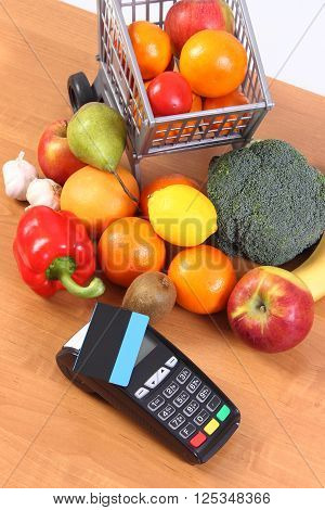 Payment terminal credit card reader with contactless credit card and fresh fruits and vegetables with plastic shopping carts cashless paying for shopping finance concept