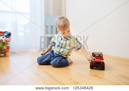 childhood, toys and people concept - little baby boy toy playing with car at home