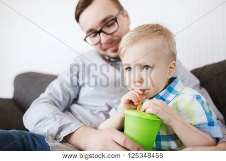 family, childhood, fatherhood, care and people concept - father helping little son with drinking from cup at home