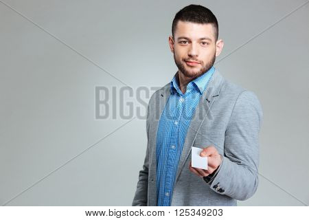 Businessman giving blank card at camera over gray background