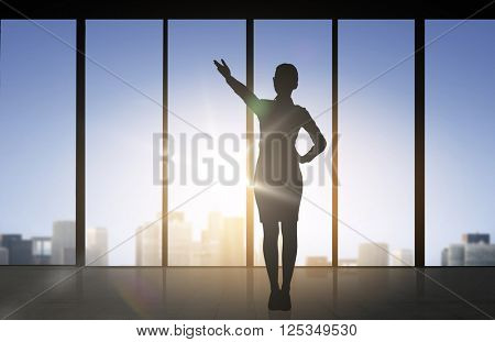 business and people concept - silhouette of woman pointing hand and showing direction over office window background