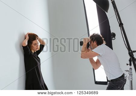 Man photographing female model in professional studio with equipment