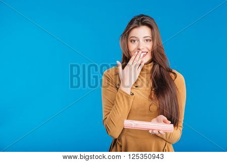 Wondered attractive young woman holding small pink present box over blue background