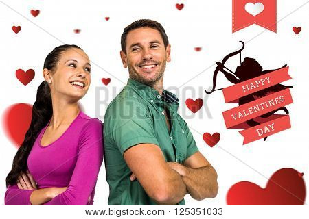 Smiling couple standing back to back with arms crossed against happy valentines day
