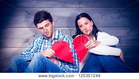 Young couple sitting on floor with broken heart against bleached wooden planks background