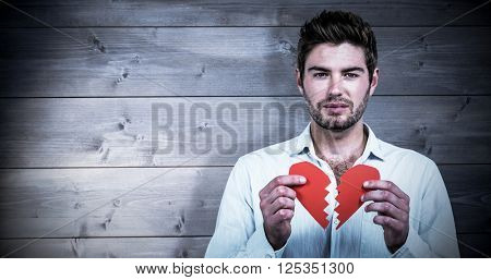 Sad man holding heart halves against bleached wooden planks background