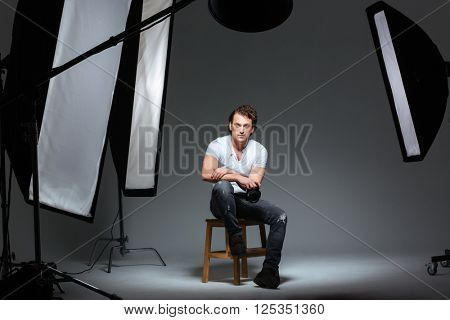 Serious male photograph sitting on the chair in professional studio and looking at camera