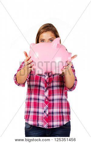 Young woman holding big piggybank