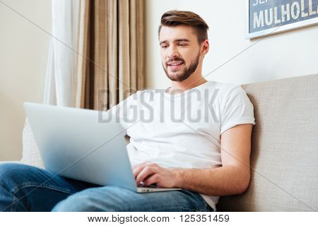 Handsome man using laptop computer on the couch at home
