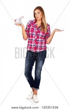 Young woman holding shopping trolley and gesturing dont know