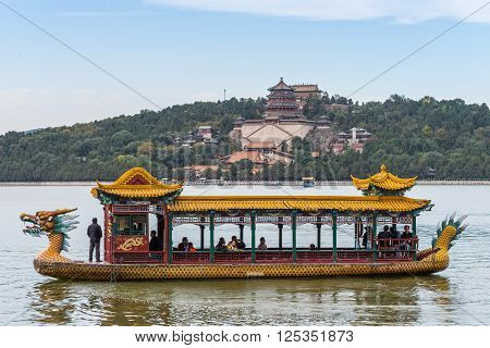 Beijing China - October 14 2013: Tourists on a dragon boat floating on the Kunming Lake Beijing China. Summer Palace in the background.