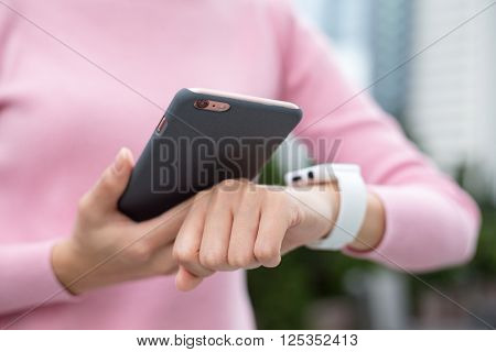 Woman using smart watch and connecting with cellphone