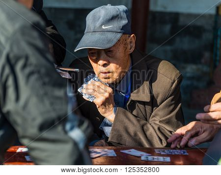 Beijing China - October 15 2013: Portrait of a Elderly Chinese men enjoying a game of cards with friends in the surroundings of the Temple of Heaven in Beijing China.