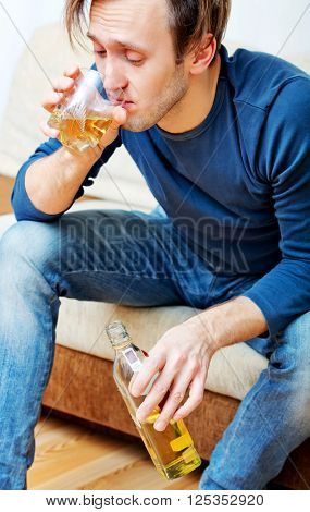 Drunk man sitting on couch and drinking whiskey