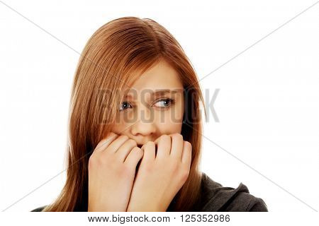 Stressed teenage woman biting nails