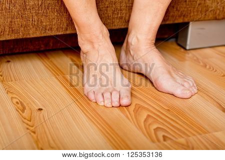 Feet of old woman on the floor