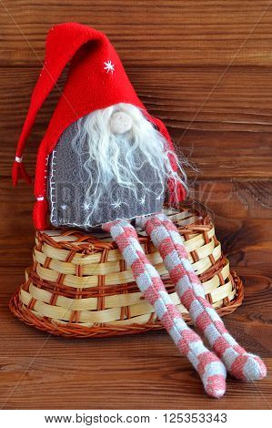 Scandinavian Christmas gnome - stitched toy. Basket. Brown wooden background