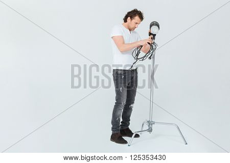 Male photographer preparing lighting equipment isolated on a white background