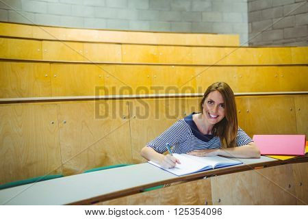 Mature student taking notes in lecture hall at the university