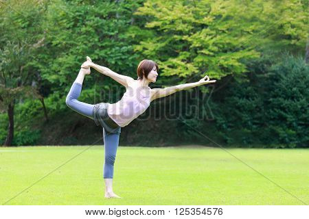 Japanese woman outside doing yog Lord of the Dance Pose