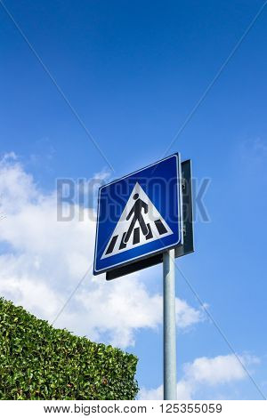 Pedestrian crossing sign with blue sky in background and green hedge.