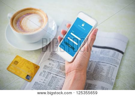 Credit Card against woman holding mobile phone by coffee and newspaper in cafe