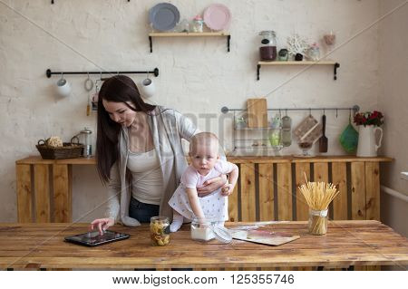 Mom and daughter together online shopping working mom using tablet computer in home interior lifestyle real