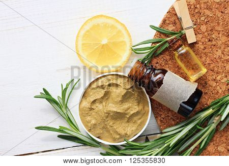 Cosmetic clay facial mask, rosemary oil and herbs, lemon. Body wrap domestic treatment. Top view.