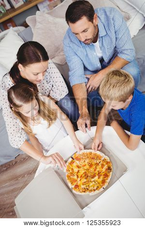 High angle view of family taking pizza slices on table at home